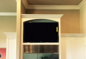 TV Mounted above refrigerator in kitchen