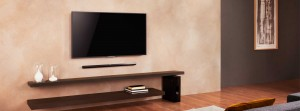 Soundbar mounted below TV with sub-woofer placed next to console